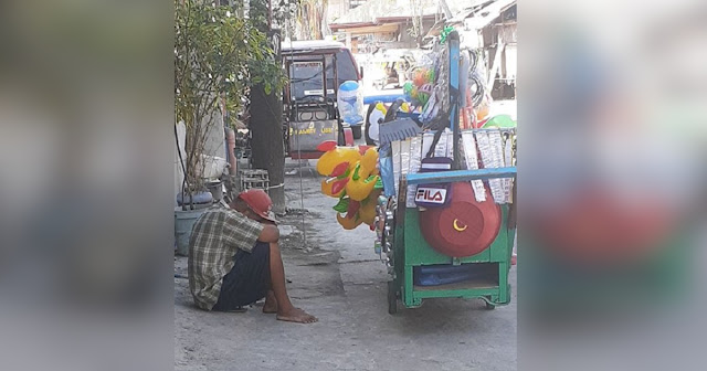 Heartbreaking Photo of Tired Vendor Sleeping Beside the Street Goes Viral
