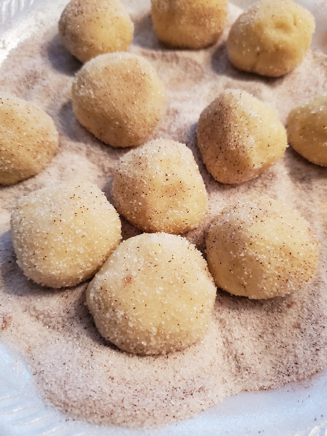 snickerdoodles are cookies rolled in cinnamon sugar and baked these are a dozen of them in the sugar