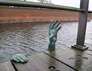γλυπτό στη Δανία. Δείχνει έναν μετανάστη  που ζητάει βοήθεια την ώρα πνίγεται.