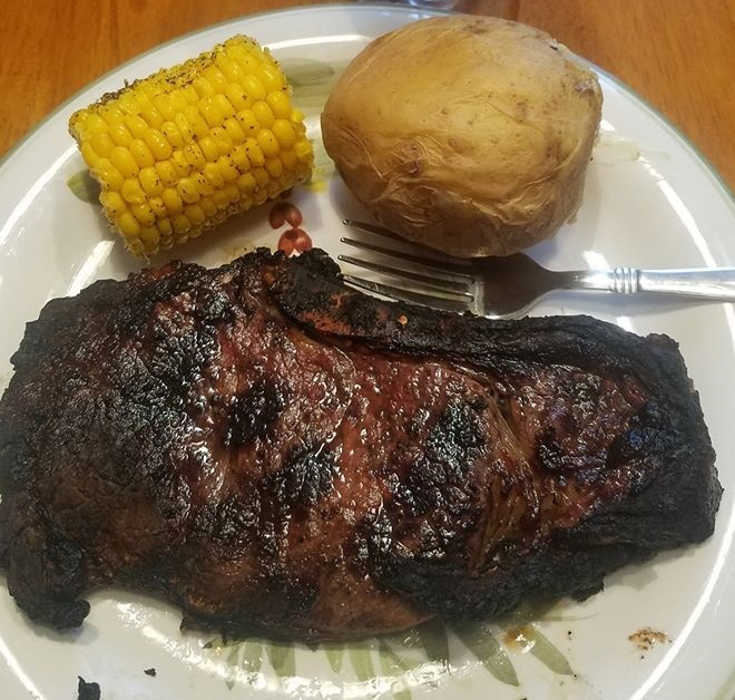 this is a medium grilled ribeye steak with baked potato and corn on the cob