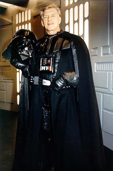 David Prowse posing on a STAR WARS set as Darth Vader.