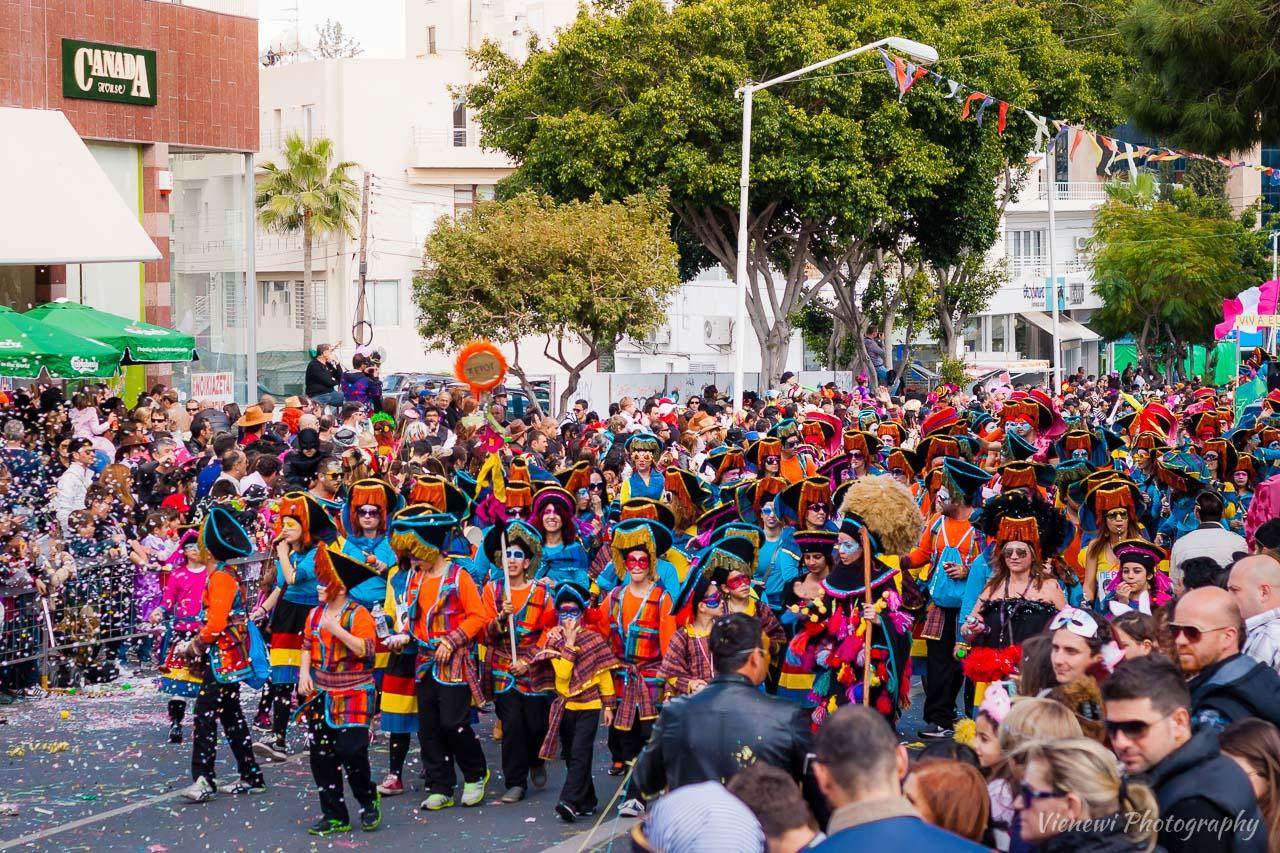 Grupa dzieci z rodzicami i nauczycielami przebrana w tematyczny kostium podczas parady karnawałowej. Po obu stronach ulicy stoją obserwujący i bawiący się ludzie.
