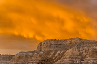 Cramer Imaging's fine art landscape photograph of fiery orange fireball in the clouds above the mountains of Cannonville Utah