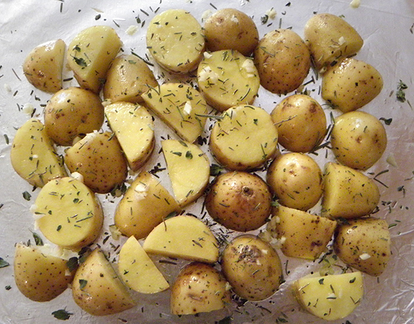 Potatoes on foil covered with herbs and garlic