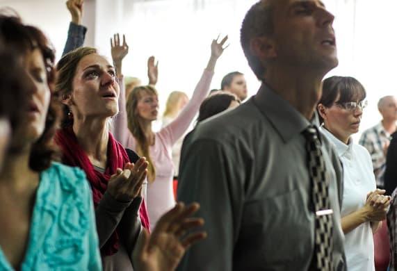 A imagem mostra fiéis em culto louvando ao senhor Deus