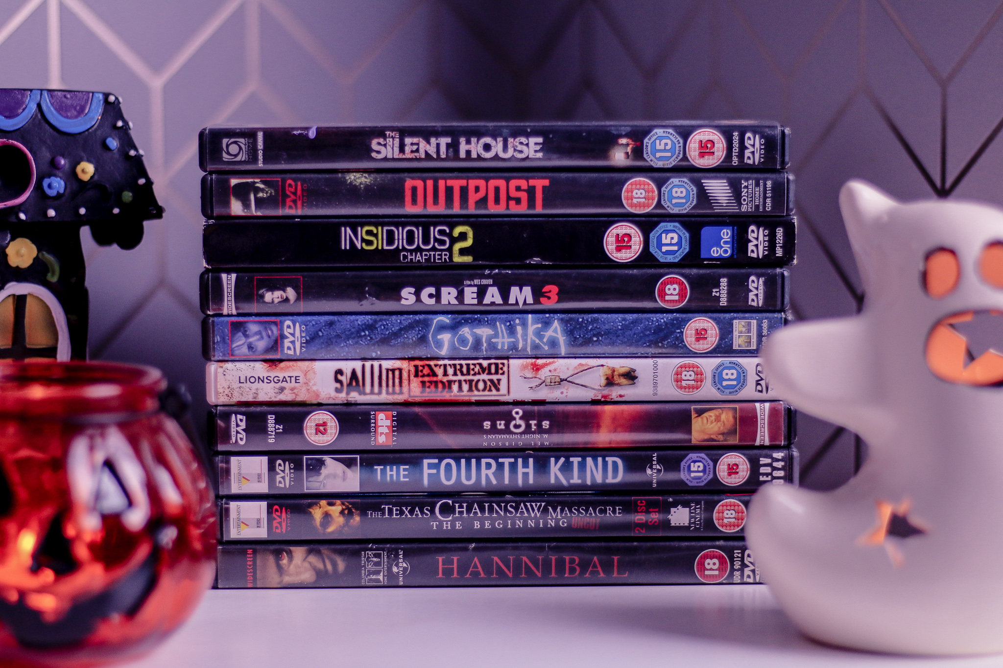Close up of 10 horror movie dvds stacked on top of each other on a white bed side table