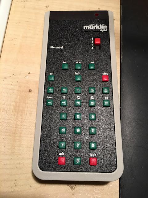 Auf dem hellbraunen Tisch liegt die IR control. Der Rahmen ist hellgrau. Die Oberfläche schwarz. Oben eher eckig. Unten abgerundet. Oben rechts ist eine rote LED, darunter das Märklin Logo. Darunter ein Schiebe-Schalter der von 1 bis 4 schalten kann. Dann folgen überwiegend grüne Tasten für Geschwindigkeit, Funktionen und Adresse. Stop ist rot.