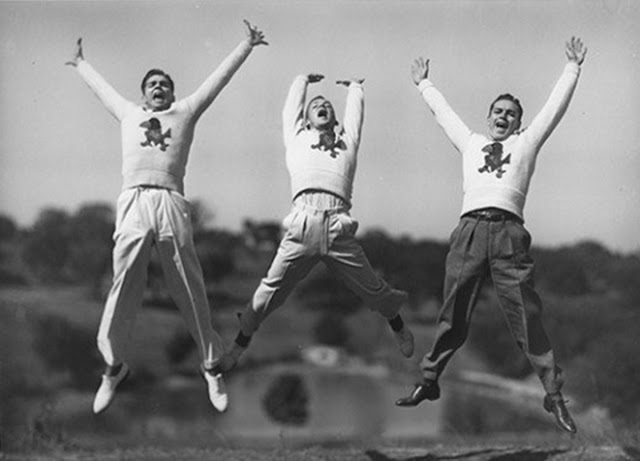 Three male cheerleaders c 1940s mid jump. Pom-Pom Mom. marchmatron.com