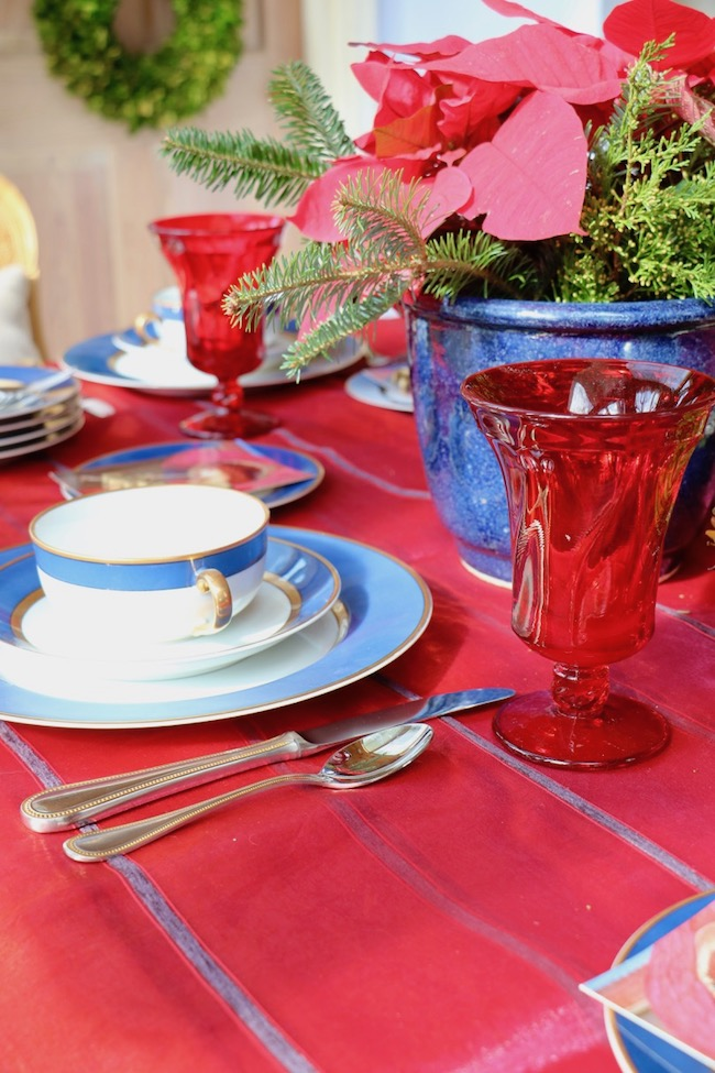 A navy clay pot holds red poinsettias as a centerpiece on the Christmas Red and Navy Blue Table Setting
