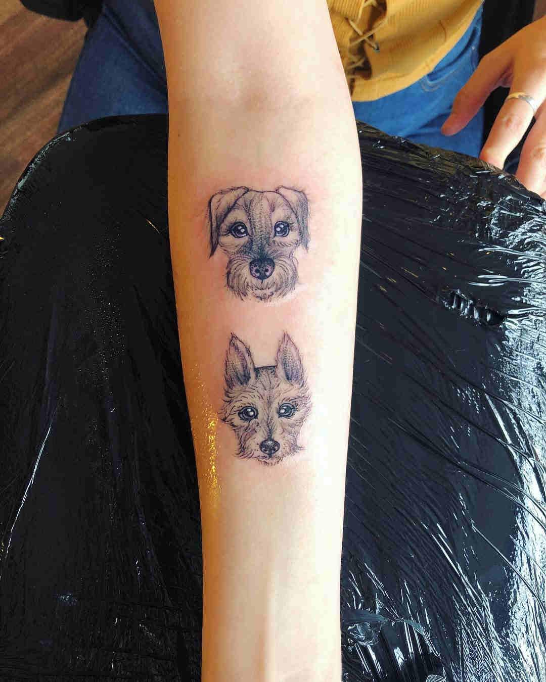 Precioso tatuaje de dos perritos en el antebrazo de una chica