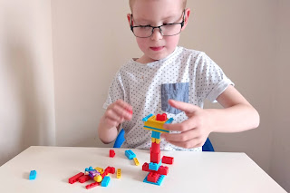 A blonde haired boy wearing glasses and a white short sleeved t-shirt with small blue + signs and a denim front pocket on the right side.He is sat at a white table on a blue chair building various coloured small Bricks from Brix Play into a tower