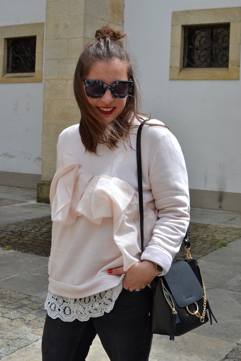 sweat cos a volant rose pastel, lunette de soleil jimmy fairly, jean noir Mango, sac style Cloé