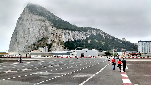 Photo of pedestrians and a cyclist crossing the runway of the Gibraltar airport. The road crossing the runway is the only land route in or out of the British territory which borders Spain.