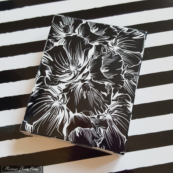 black and white cardboard box with floral pattern on striped background