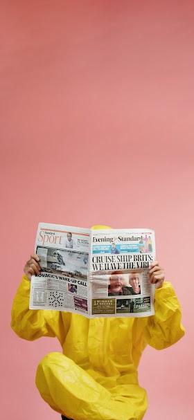 خلفية شخص بمعطف بلاستيكي اصفر يقرأ جريدة