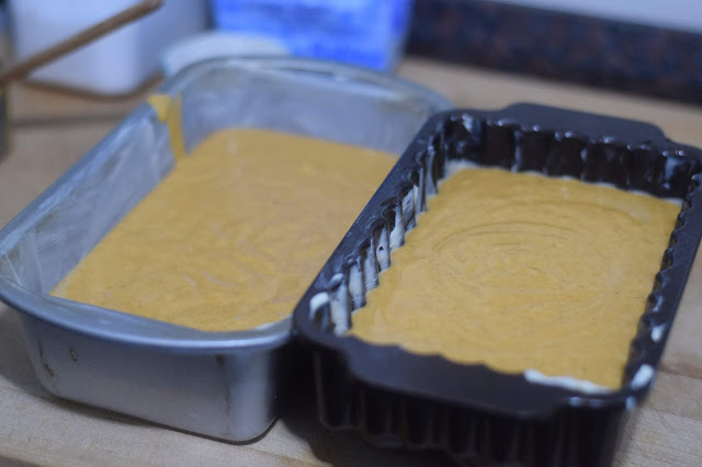 The pumpkin bread batter distributed evenly between two bread pan.