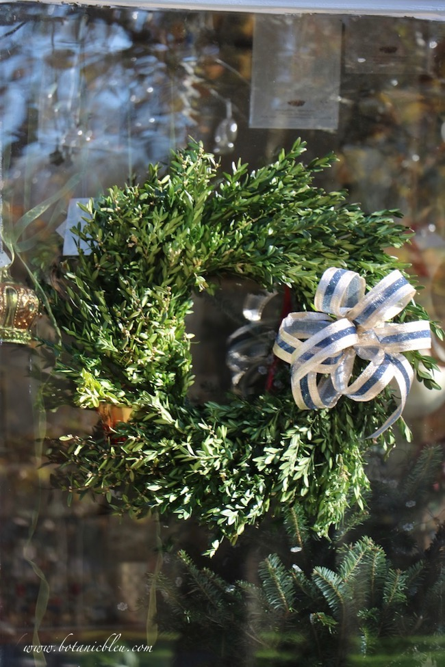 Wired gold and dark blue ribbon provides shimmer to wreaths on the French Country Christmas garden shed greenery