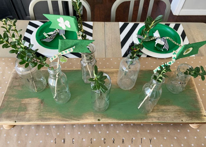 St Patrick's Day Table Centerpiece - wooden riser with glass bottles.