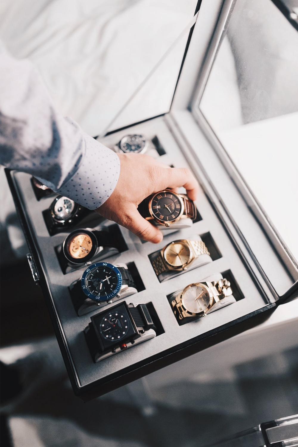 a close up picture of a hand choosing watch