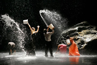 Dancers with buckets of water splashing each other