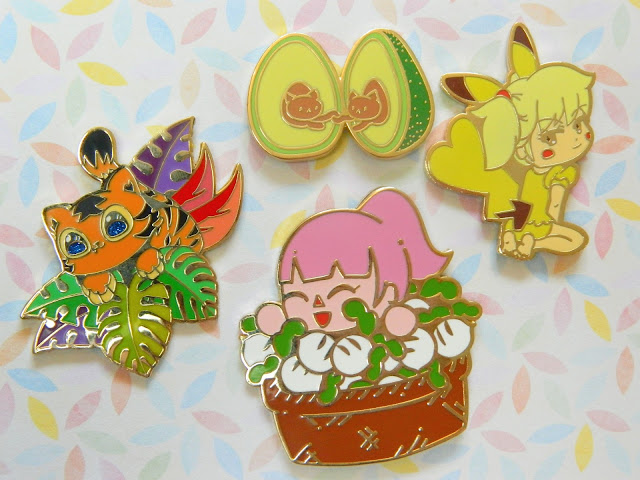 A collection of four pin badges made by Stami Studios