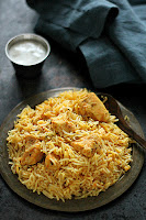 Hyderabadi Boneless Chicken Biryani in a metal plate beside a bowl of raita.
