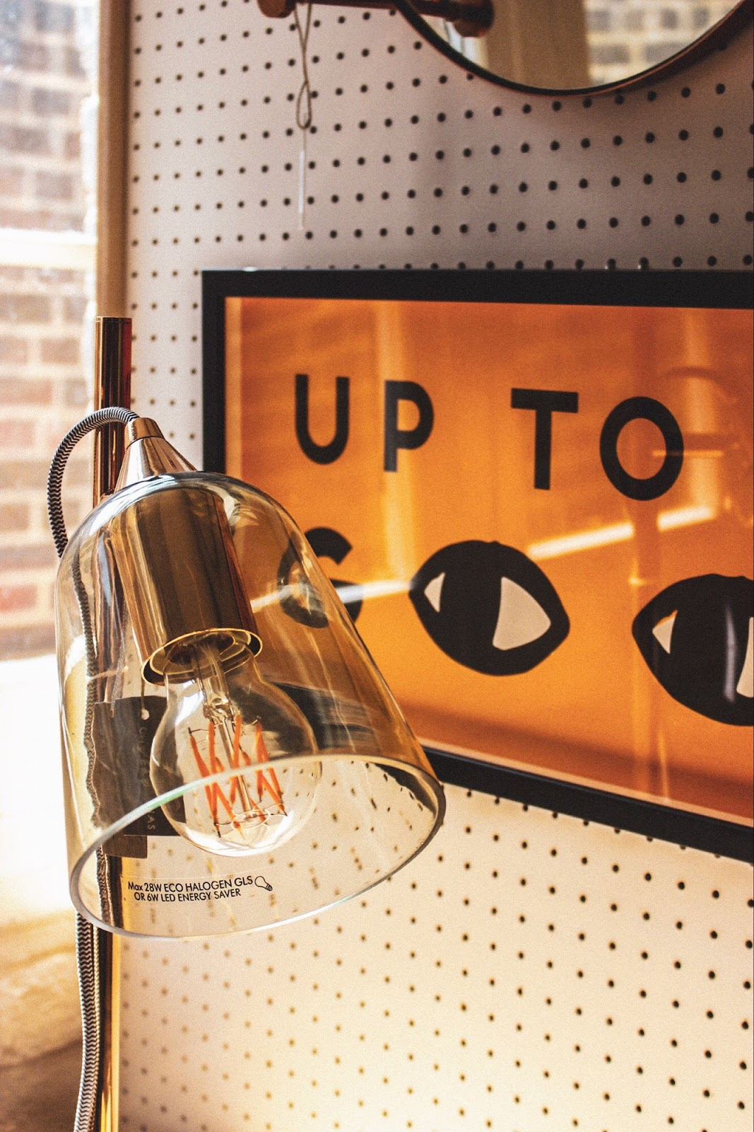 A shot of an office lamp and wall art reading 'up to no good' in Oliver Bonas