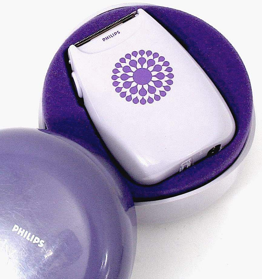 a color photograph close-up of a purple 1960s Philips shaver for young women, with starburst