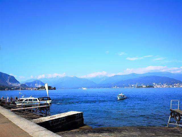 Lago con barche e monti sullo sfondo