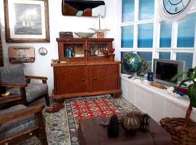 1/12 scale modern miniature lounge scene with two mid-century modern armchairs in grey with dark stained arms and legs, an early twentieth century cupboard, a battered sea chest and afghan rug on the floor. On the wall is a framed picutre of a boat and an abstract landscape. On the windowsill is a globe, several piles of books, some shells, a telescope and a flat-screen TV.