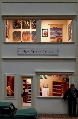 One-twelfth scale modern miniature two-storied art gallery and art supplies shop, taken from the outside at dusk. The lights are on and there is a woman in the gallery and a man standing outside on the street.