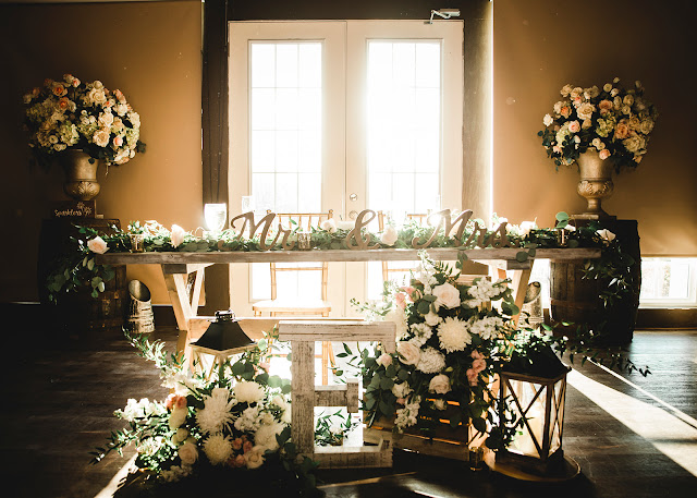 sweetheart table with flowers and wooden decor