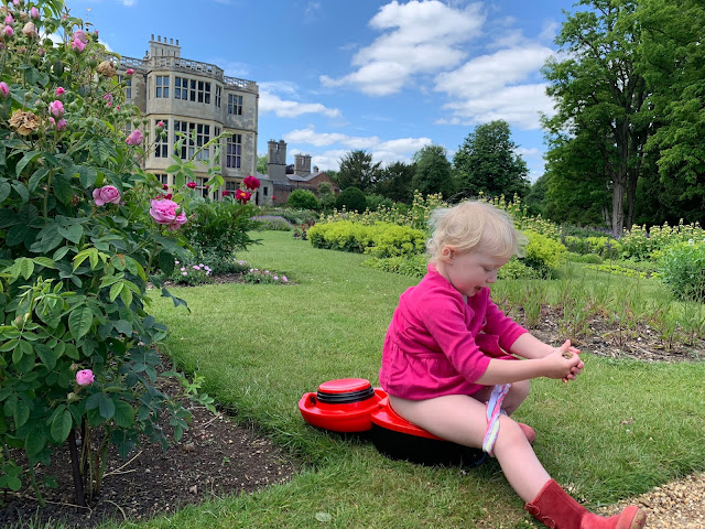A toddler sitting on a red ladybird My Carry Potty in a formal garden with a historic house in the background