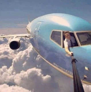 Pilot taking a selfie out of plane window while flying