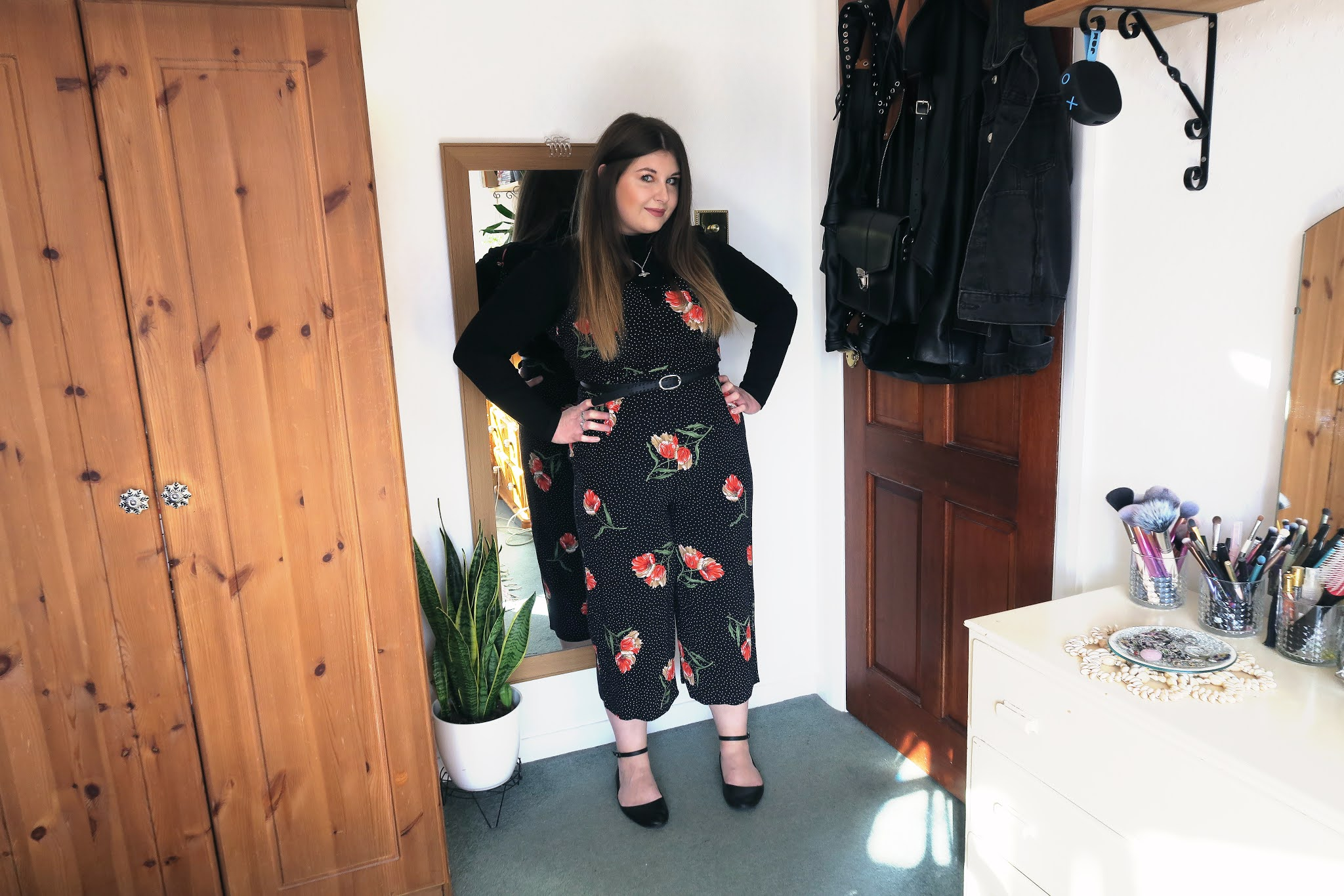 Grace is wearing a black roll neck top underneath a long black and red floral playsuit.