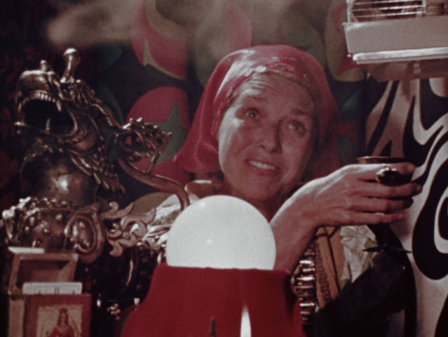 A fortune teller in red addresses her visitors