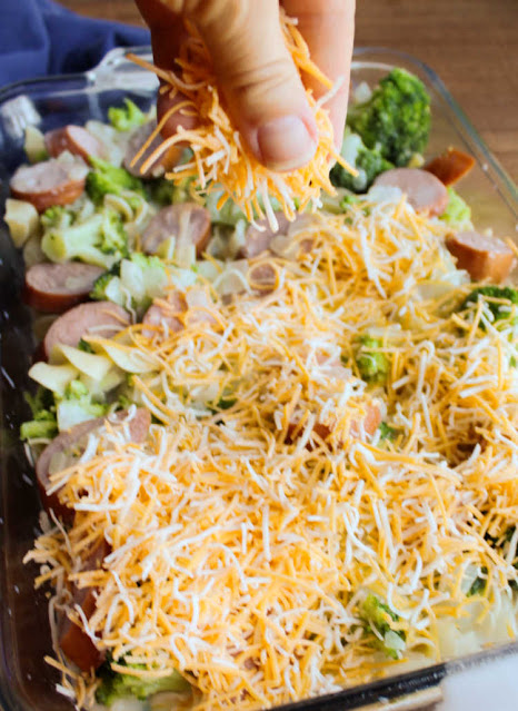 sprinkling cheese over broccoli, pasta and sausage