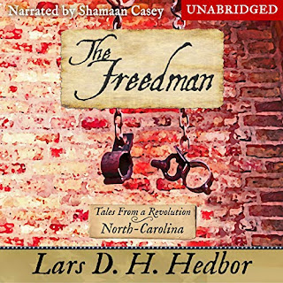 Audiobook cover of The Freedman: Tales From a Revolution - North-Carolina. A pair of manacles hang in front of a brick wall.