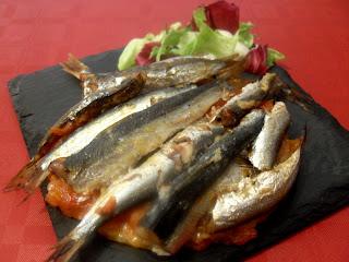 Coca de sardinas sobre ensalada.