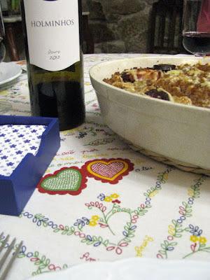 mesa posta com travessa de bacalhau e garrafa de vinho