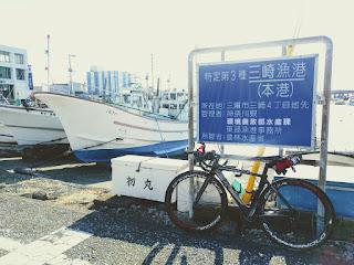 漁船と三崎漁港の標識に立てかけた黒いロードバイク