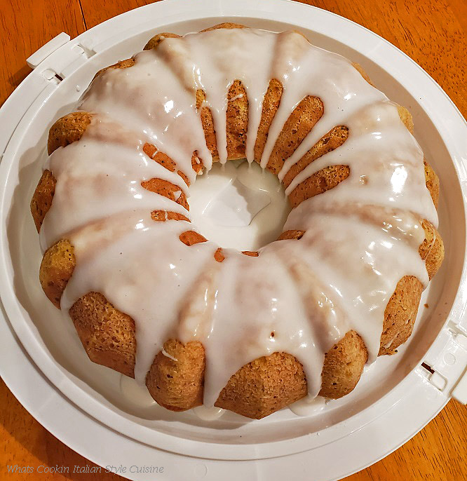 This is a top view of a baked zucchini almond and poppy seed bundt cake frosted with white frosting