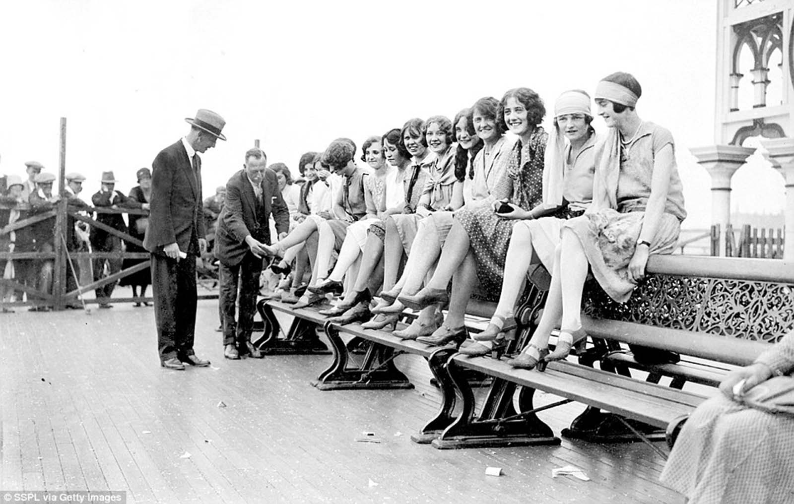 Judges judging ankles in the most beautiful ankles competition held on Palace Pier in connection with the Brighton carnival celebrations.