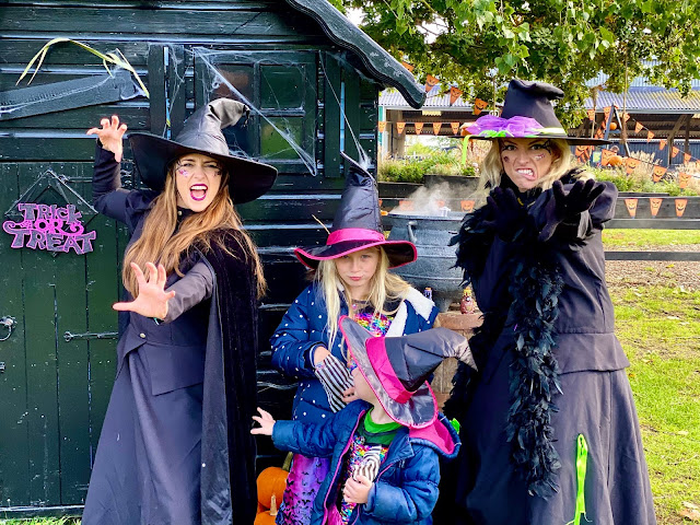 2 ladies dressed as witches in black with 2 children dressed as witches in between in the back a cauldron is bubbling