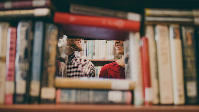 a couple seen through a bookshelf