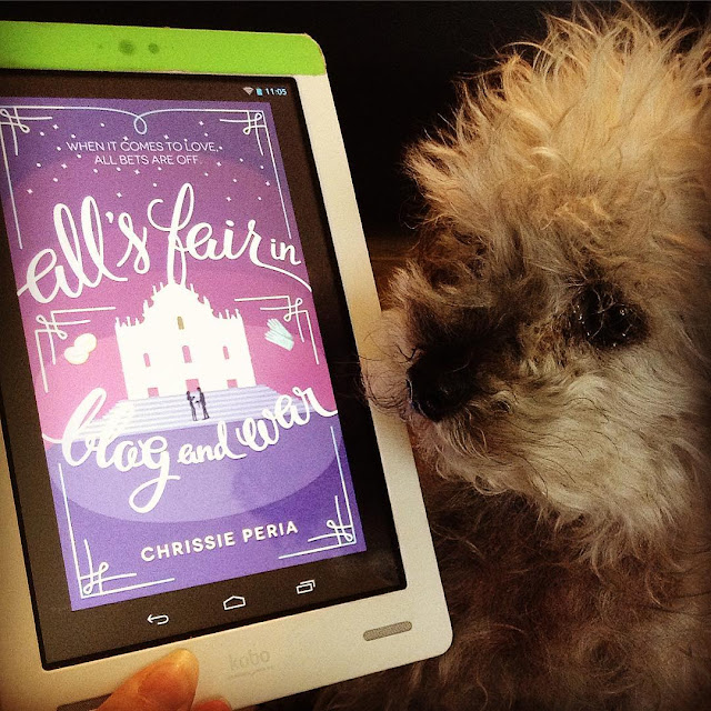 Murchie hovers beside a white Kobo with the cover of All's Fair In Blog and War on its screen. The purple cover features a stylized drawing of two people silhouetted outside a ruined cathedral.