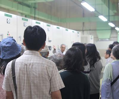 博物館の電気室で、スタッフが受変電設備について、バックヤードツアー参加者の皆さんに説明している様子(2018年5月撮影)