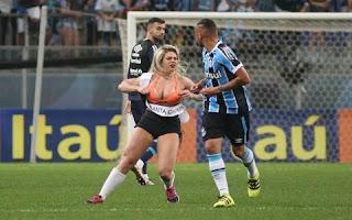 De acordo com reportagem do UOL, chama-se Kamilla Barzagli, modelo de 27 anos. Essa é a segunda vez que a modelo faz isso. A primeira aconteceu em Brasília no jogo do Flamengo contra o Palmeiras.