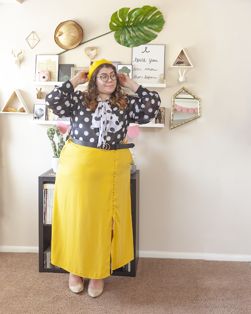 An outfit consisting of a yellow beret, a white on black polka dot blouse with a black on white polka dot neck tie attached, tied in a bow, tucked into a yellow button down midi skirt and beige slingback heels.