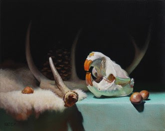 Rodent Skull and antlers lying on a green tablecloth and white fur, nuts scattered around